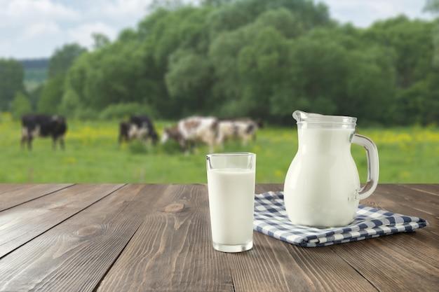 Парное молоко в стекле на темном деревянном столе и запачканном ландшафте с коровой на луге. здоровое питание. деревенский стиль Premium Фотографии