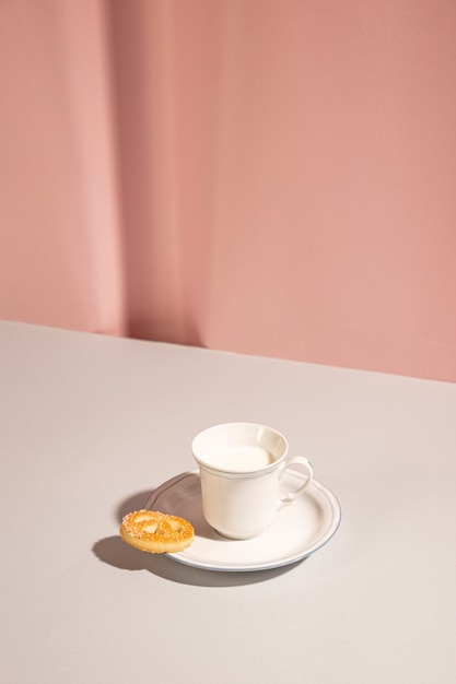 Fresh milk with sweet cookie on table against pink backdrop Free Photo
