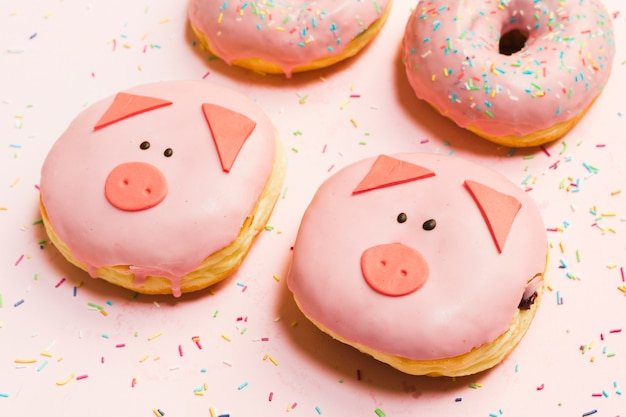 Fresh mini pig donuts glazed with cream over pink backdrop Free Photo