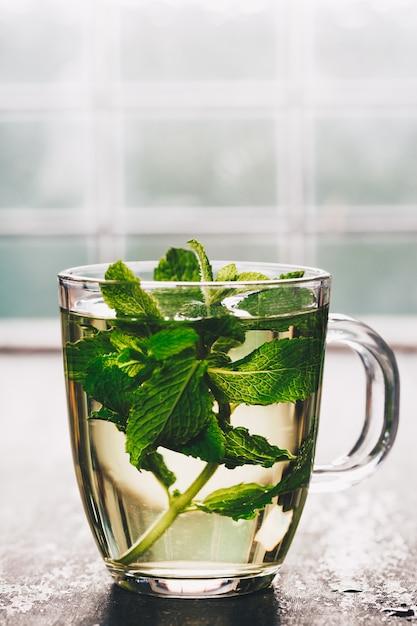 Fresh mint tea near the window. cozy home or health Premium Photo