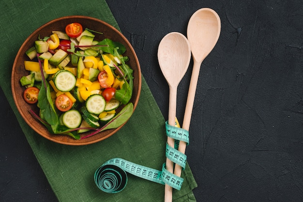 Fresh mixed vegetable salad with wooden spoon and measuring tape on green napkin over concrete backdrop Free Photo