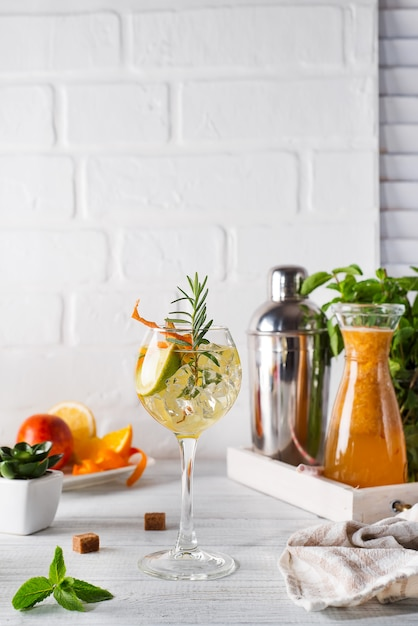 Fresh mojito drink with rosemary, lemon and orange on white wooden backgorund, copy space Premium Photo