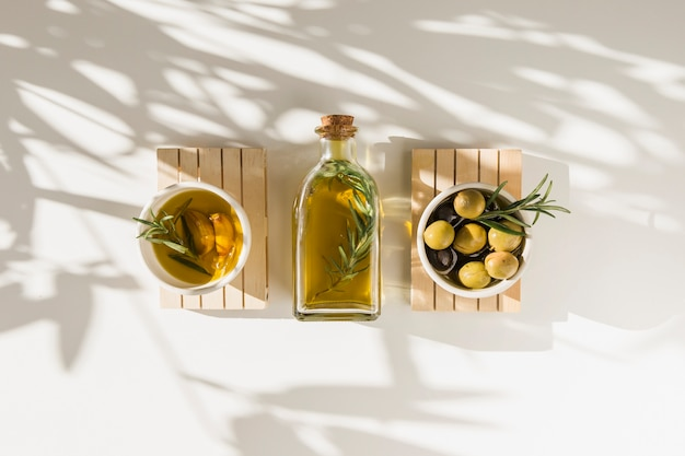 Fresh olives with oil bottle on white backdrop Premium Photo