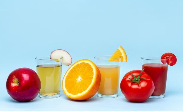 青いサーフに新鮮なオレンジ、リンゴ、トマトジュース。健康で自然な飲み物。食事とビタミン Premium写真