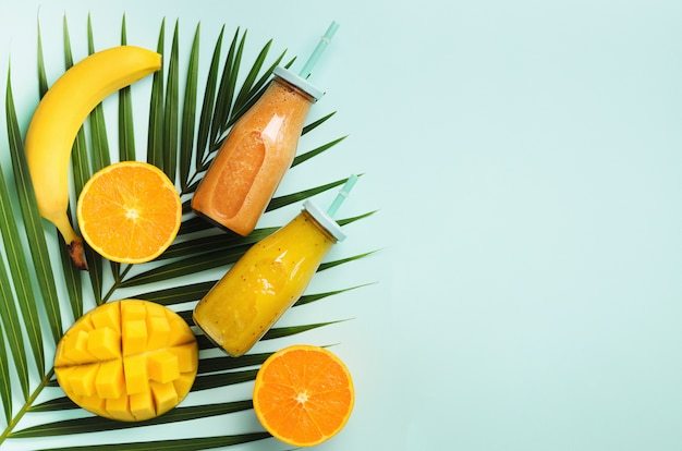 Fresh orange, banana, pineapple, mango smoothie and juicy fruits on palm leaves over blue background. detox summer drink. Premium Photo