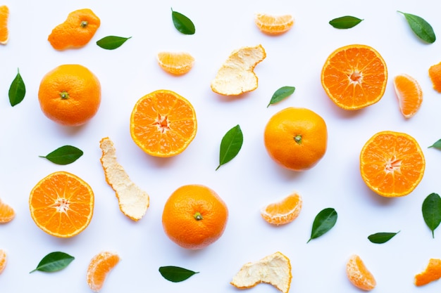 Fresh orange citrus fruit with peel and green leaves on white Premium Photo