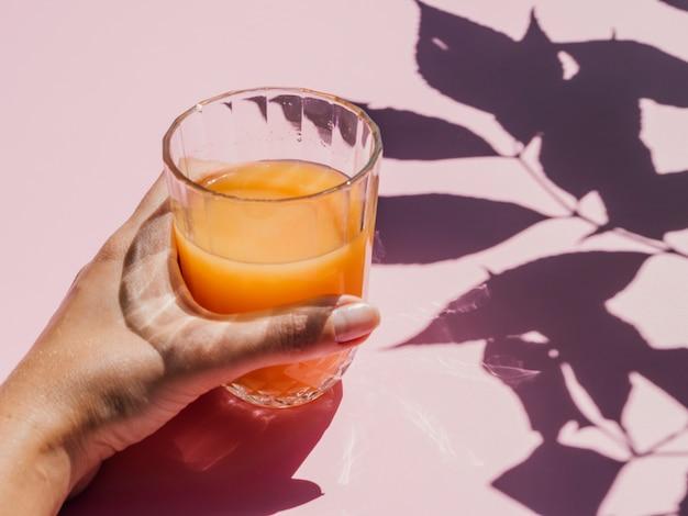 Fresh orange juice in glass and shadows Free Photo
