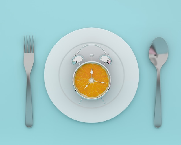 Fresh orange slice alarm clock on plate with spoons and forks on blue color. minimal conce Premium Photo