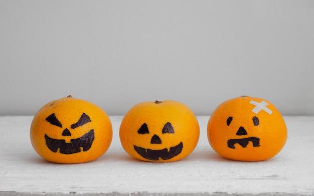 Свежий апельсин с головкой тыквы преследуют жуткое лицо, легкое украшение diy для хэллоуина Premium Фотографии
