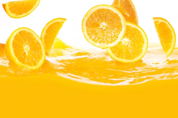 Fresh oranges falling in juice Free Photo