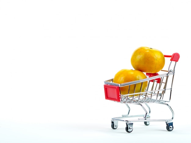 The fresh oranges and shopping cart Premium Photo