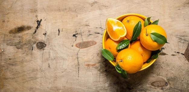 カップの葉と新鮮なオレンジ。 Premium写真