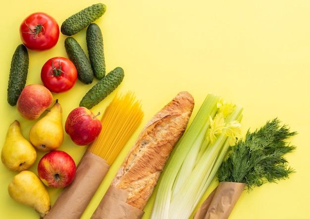 Свежий органический хлеб, овощи, зелень и фрукты, крупы и макароны на желтом столе. концепция питания экологической фермы. вид сверху. плоская планировка Premium Фотографии
