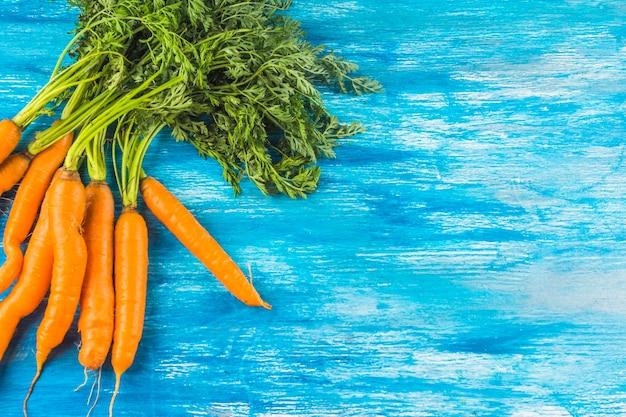 Fresh organic carrots on blue wooden background Free Photo