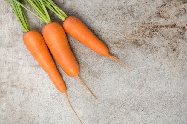 Fresh organic carrots with green tops on rustic table. copy space. top view. Premium Photo