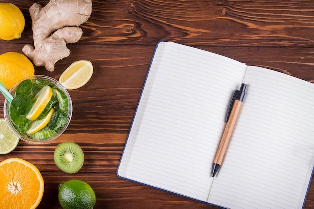 Свежие органические фрукты и открытый пустой блокнот и ручка на деревянных фоне. концепция здорового питания и здорового образа жизни. вид сверху Premium Фотографии