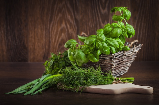 Fresh organic green herbs on wood Free Photo
