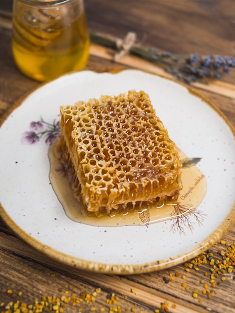 Fresh organic honeycomb on plate with bee pollens over table Free Photo