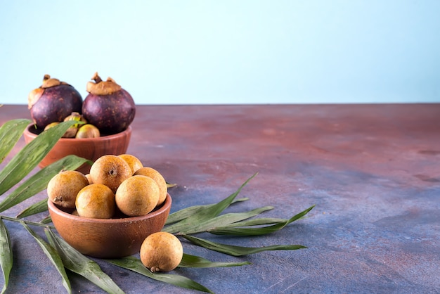 Fresh organic lychees with palm leaf in a bowl on stone background. raw diet or vegan food concept. Premium Photo