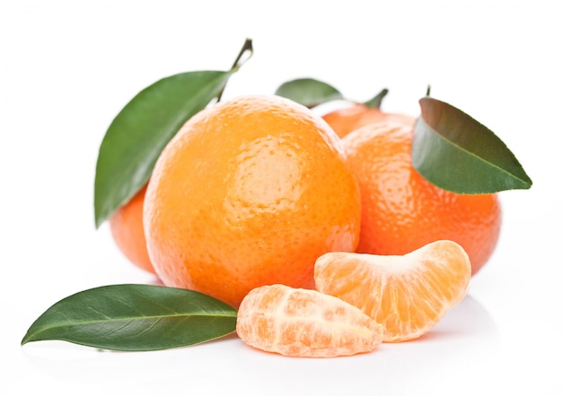 Fresh organic mandarins tangerines fruits with leaves with peeled halves on white background Premium Photo