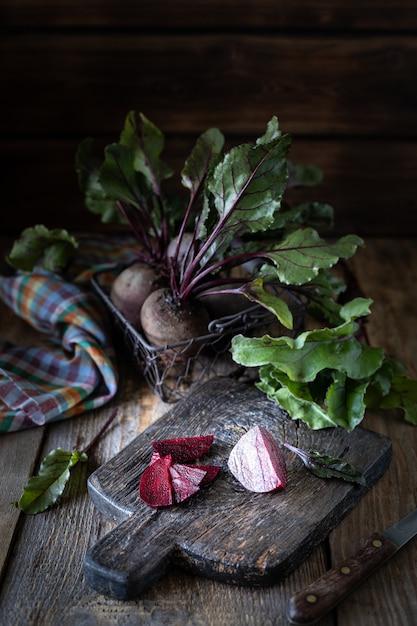 Barbabietole rosse organiche fresche con foglie in un cesto di vimini su un tavolo di legno. ortaggi biologici naturali. vendemmia autunnale. rustico Foto Gratuite