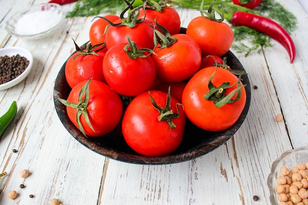 Fresh organic red tomatoes in black plate on white wooden table with green and red and chili peppers, green peppers, black peppercorns, salt, close up, healthy concept Free Photo