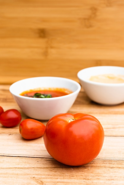 Fresh organic tomatoes and sauce on wooden table Free Photo