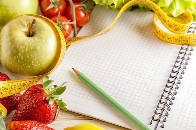 新鮮な有機野菜や果物、開いた空白のノートと木製のペン Premium写真