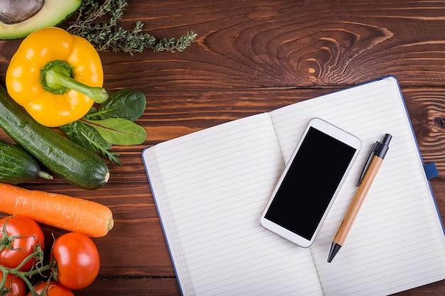 Свежие органические овощи и фрукты. перец, помидор, авокадо, открытая пустая тетрадь, телефон и ручка на деревянном фоне. концепция здорового питания и здорового образа жизни. вид сверху Premium Фотографии