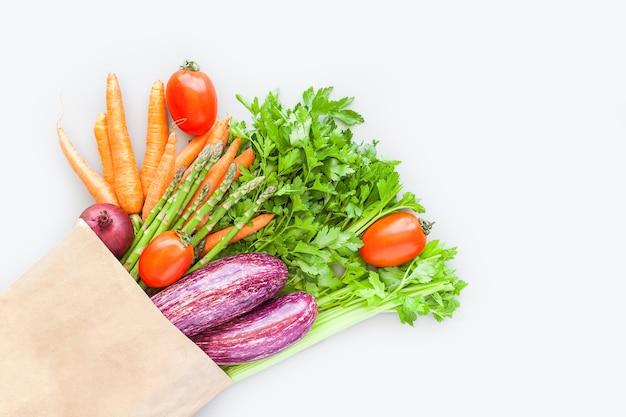 Свежие органические овощи в бумажной хозяйственной сумке eco craft в плоской планировке, вид сверху с копией пространства на сером фоне. устойчивый образ жизни. без отходов, без пластика, пакет услуг, концепция пожертвования Premium Фотографии