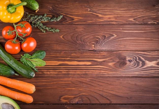 Свежие органические овощи. перец, помидор, авокадо, на деревянных фоне. концепция здорового питания и здорового образа жизни. вид сверху. Premium Фотографии