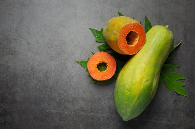 Papaia fresca, tagliata a metà, messa sul pavimento scuro Foto Gratuite