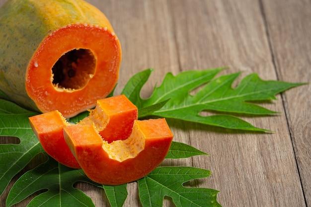 Papaia fresca, tagliata a pezzi, messa su un pavimento di legno Foto Gratuite