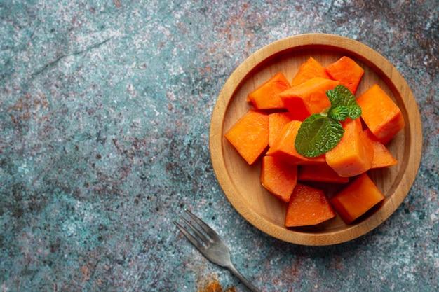 Papaia fresca, tagliata a pezzi, messa su un piatto di legno. Foto Gratuite