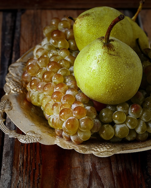 Fresh pears and green grapes. autumn nature concept. Free Photo