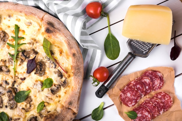 Fresh pepperoni with vegetables; cheese; grater and delicious pizza over wooden panel Free Photo
