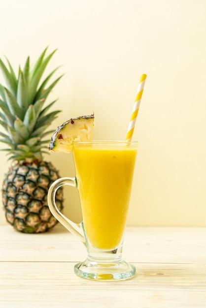 Fresh pineapple smoothie glass on wood table Premium Photo