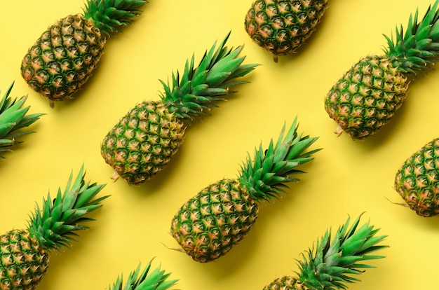 Fresh pineapples on yellow background. pop art design, creative concept. bright pineapple pattern for minimal style. Premium Photo