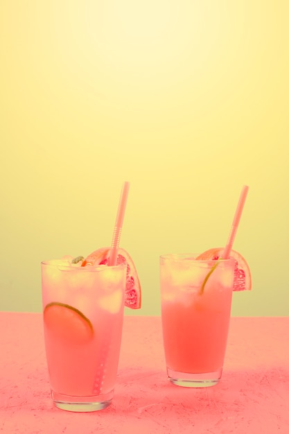 Fresh pink alcoholic cocktail with grapefruit; lemon slice and ice cubes against yellow background Free Photo
