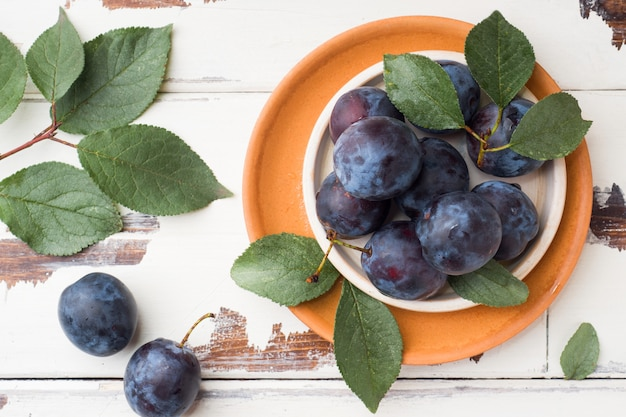 Fresh plum berries on a plate with leaves Premium Photo