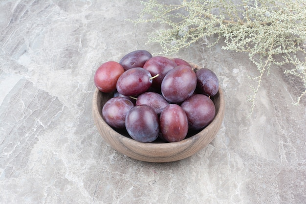 Fresh plums in wooden bowl on stone background. Free Photo