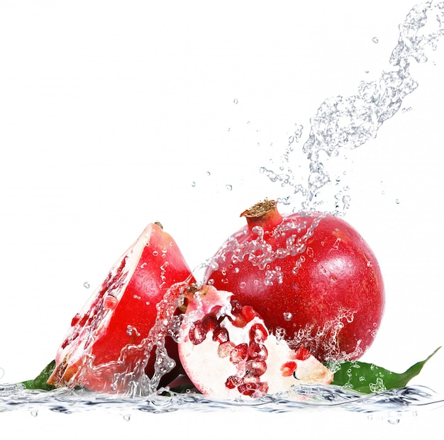 Fresh pomegranate falling in water Premium Photo