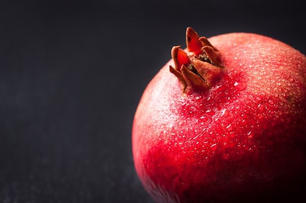 Fresh pomegranate with water droplets on a dark background Free Photo