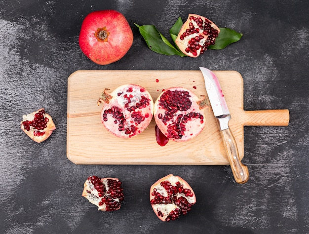 Fresh pomegranates top view with knife on wooden cutting board on dark surface Free Photo