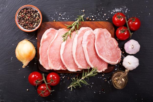 어두운 배경에서 요리 재료와 신선한 돼지 고기 프리미엄 사진