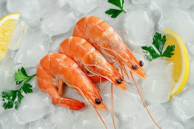 Свежие креветки на льду с кусочками петрушки и лимона. концепция средиземноморской кухни Premium Фотографии