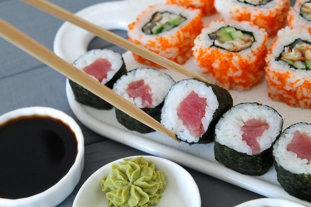 신선한 준비된 초밥. 참치와 캘리포니아 마키를 닫습니다. 스시의 일부를 복용 젓가락 테이블 레스토랑에 롤. 일본 음식을 먹는 프리미엄 사진