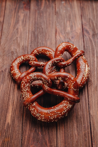 Fresh pretzel sprinkled with sesame seeds on a wooden table Premium Photo