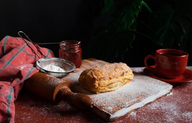 赤いカップとジャムの瓶と一緒にテーブルの上にプラムまたは赤スグリのジャムを配置した新鮮なパフ Premium写真