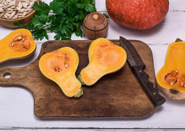Fresh pumpkin cut in half on a wooden kitchen board Premium Photo